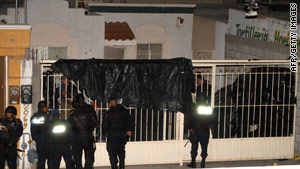 Police guard the house in Juarez, Mexico, where 14 people were shot to death on Friday night.