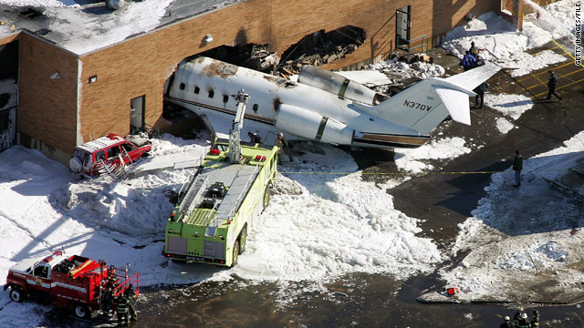 Emergency workers tend to wreckage after the crash of a charter jet at New Jersey's Teterboro Airport in February 2005.