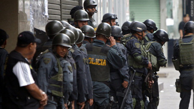 Police officers take position outside a bank in Lima, Peru, where a man was holding 33 people hostage on Friday.