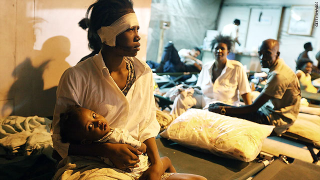 A injured women sits with her baby at a makeshift field hospital Wednesday in Port-au-Prince, Haiti.