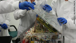Scientists carefully remove stem cells from a shelf on the Discovery shuttle after its return.