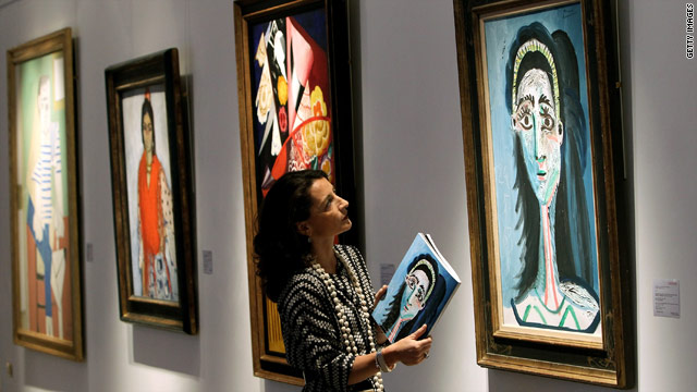 "A Christie's employee inspects a work titled ""Tete de Femme"" by Pablo Picasso, which is among works to be auctioned."