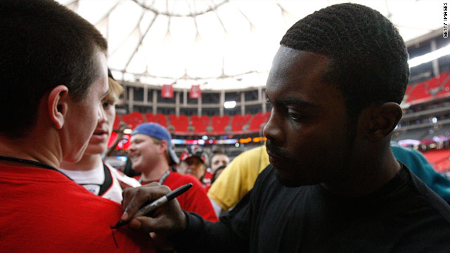 Michael Vick signs a T-shirt for an Atlanta fan before a 2009 game.