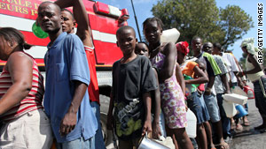 Haiti quake survivors line up to get water from a fire truck.