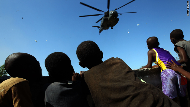 Haitian children watch a U.S. helicopter January 20 as the American mission to aid the earthquake-stricken country continues.