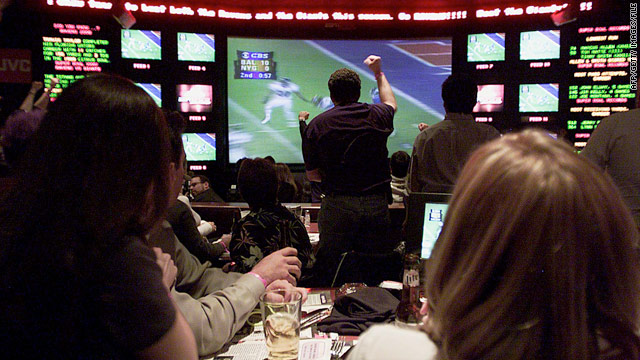 Fans cheer an interception during Super Bowl XXXV while watching the ESPN Zone's video wall in Baltimore in 2001.