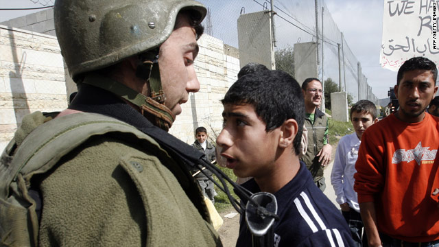 A young Palestinian protester stands face-to-face with an Israeli soldier during a March 6 demonstration seeking to remove a metal fence placed  by Israelis to separate the town of Beit Omar and the main Hebron-Jerusalem road on the West Bank.