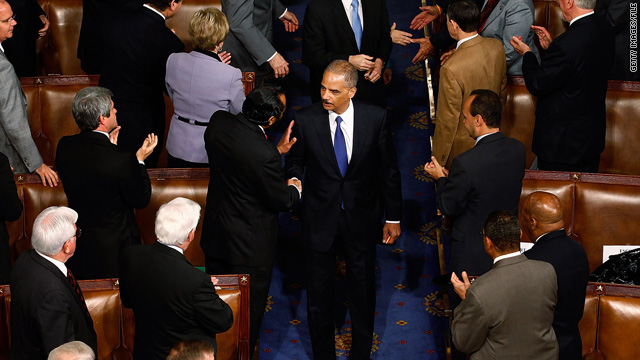 Attorney General Eric Holder, who will likely sue over Arizona law, is greeted by members of Congress May 20.