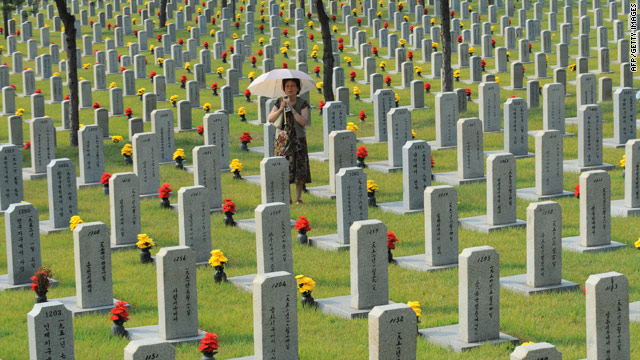 A woman looks at the tombstone of her elder brother, who died in 1951 during the Korean War, at a national cemetery in Seoul.