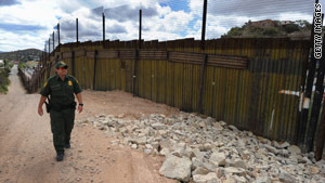A U.S. Border Patrol officer monitors the U.S.-Mexico border fence in Nogales, Arizona.