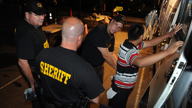An illegal immigrant is processed by Maricopa County sheriff's deputies July 29.