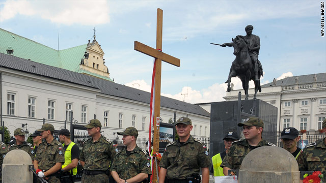 Police stand before a wooden cross dedicated to the late President Lech Kaczynski during a protest this month in Warsaw.