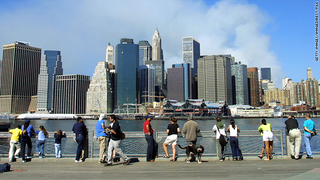 People gather near New York Harbor and watch smoke rise from the World Trade Center site on Sept. 12, 2001.