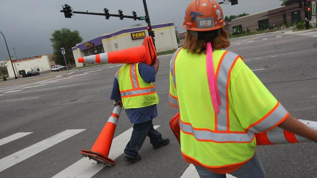 Road construction workers collect cones on a project funded by federal stimulus funds in Littleton, Colorado.