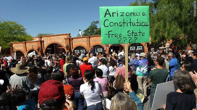 Demonstrators in Tuscon listen as U.S. Rep. Raul Grijalva, D-Arizona, denounces his state's new immigration law.