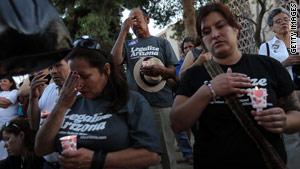 Opponents of Arizona's new immigration law pray outside the state Capitol building in Phoenix, Arizona, on Sunday.
