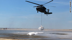 A Louisiana National Guard helicopter places sandbags Monday in Lafourche Parish to protect against oil.
