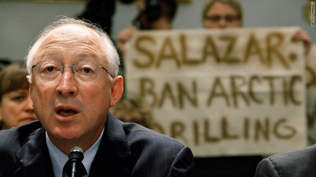 Protesters hold a sign behind Interior Secretary Ken Salazar as he testifies Wednesday before a congressional committee.