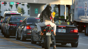 Motorcyclists wait at a traffic light as they ride without helmets in Miami, Florida.