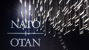 Lights hang in front of a NATO logo during the NATO Summit Friday in Lisbon, Portugal.