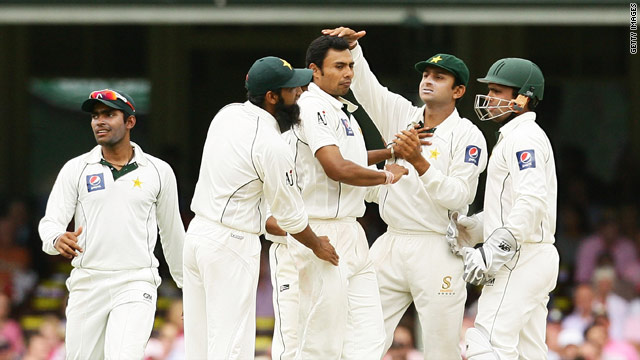 Pakistan players congratulate Danish Kaneria after he claims the wicket of Brad Haddin in Sydney.