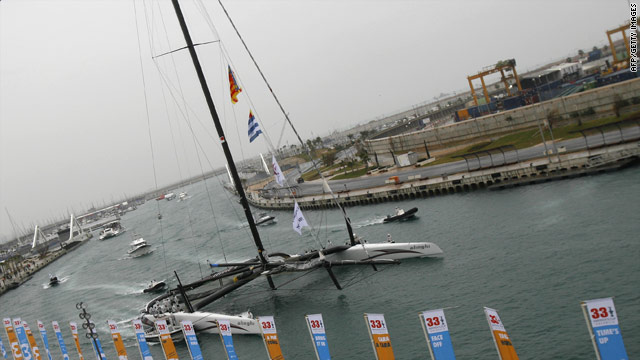 Alinghi's giant catamaran returns to Valencia's harbor after the first day of racing was postponed.