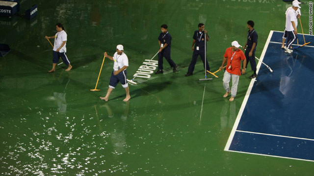 Workers try to clear water off the court as bad weather hits the Dubai Tennis Championship final on Saturday.