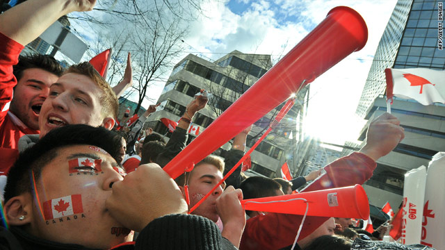 Men blow novelty horns as crowds celebrate on Robson Street in downtown Vancouver after Canada's victory Sunday.