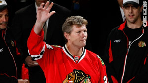 Former Blackhawks and Red Wings player Bob Probert waves before a ceremonial faceoff at a 2009 playoff game.