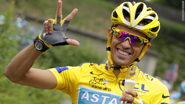 Spanish cyclist Alberto Contador celebrates his triumph with the traditional glass of champagne in Paris.