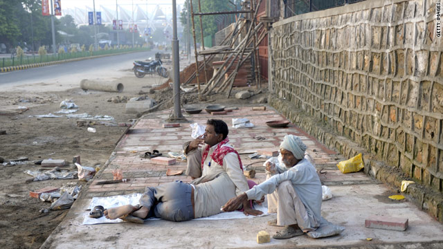 Indian laborers sit on the semi-finished pavement heading to Jawarhal Nehru Stadium in New Delhi on September 25 ahead of the upcoming Commonwealth Games.