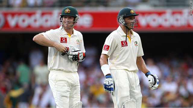 Brad Haddin (left) and Michael Hussey walk off as bad light brings play to an early close at the Gabba.