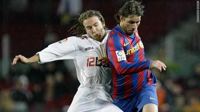 Sevilla's cup hero David Capel, left, battles for the ball with Barcelona defender Maxwell.