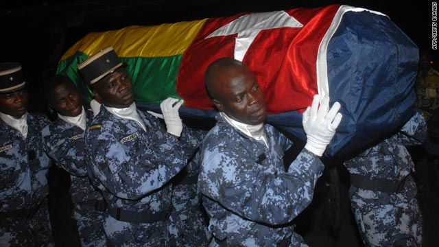 Togolese gendarmes carry a coffin containing one of the victims of the gun attack in Angola.