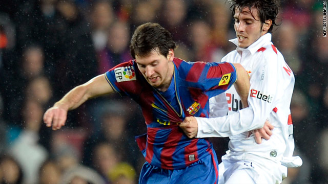Sevilla's French defender Julien Escude struggles to get to grips with Barcelona's two-goal hero Lionel Messi.