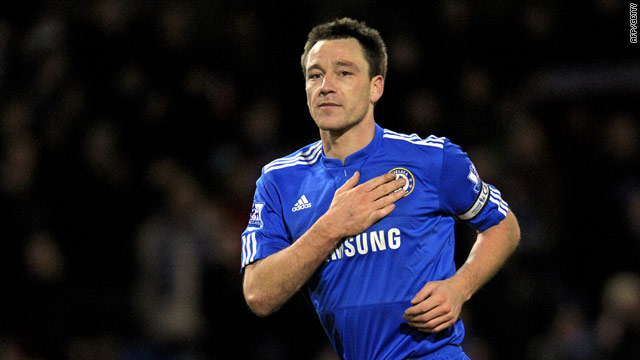 Chelsea captain John Terry touches his club's badge after scoring their winner at Burnley.