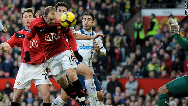 In-form England striker Wayne Rooney climbs to power home Manchester United's first goal against Portsmouth.