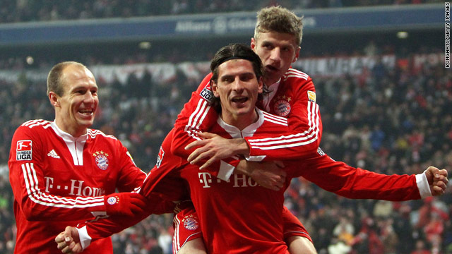Goalscorers Arjen Robben, left, and Mario Gomez, right, celebrate along with Bayern teammate Thomas Mueller.