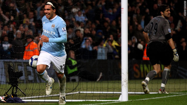 Carlos Tevez celebrates his third goal for Manchester City against Wigan.