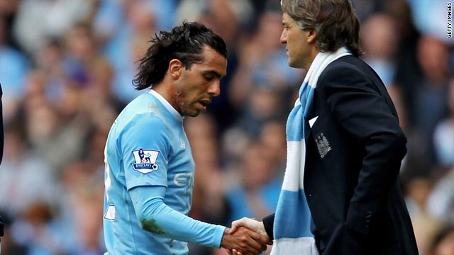 Carlos Tevez shakes hands with manager Roberto Mancini, who he has criticized, after being substituted on Saturday.