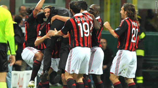 Milan coach Leonardo is mobbed by team-mates after the opening goal in their 3-0 victory over Juventus.