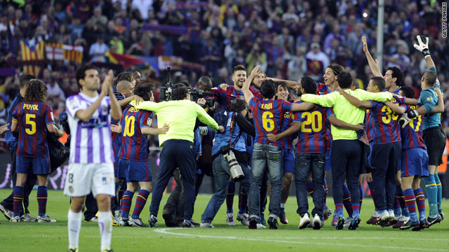 Barcelona players celebrate their fourth title success in six years after thumping Valladolid 4-0 at the Nou Camp.