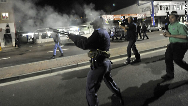 A police officer fires tear gas at protesting workers near the Moses Mabhida stadium in Durban on June 14.