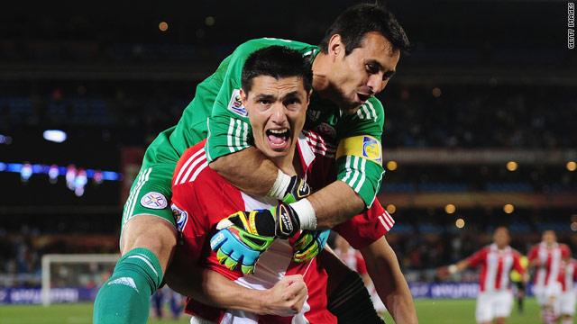 Oscar Cardozo celebrates his winning penalty with Paraguay goalkeeper Justo Villar.