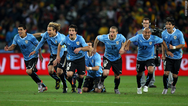 The Uruguay players begin their charge after Sebastian Abreu scored the winning penalty.