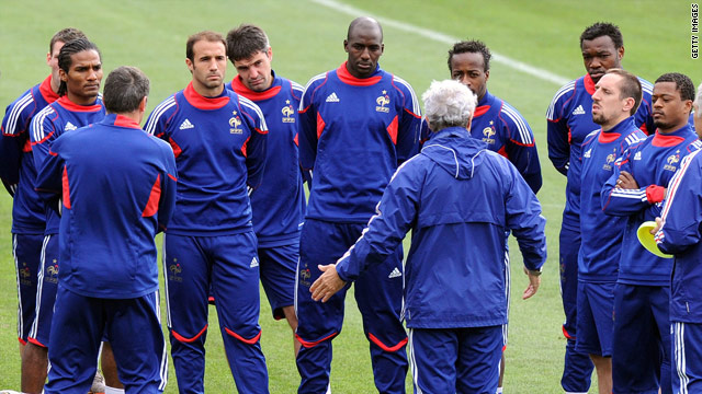 The French team listen to former coach Raymond Domenech (center), Franck Ribery and Patrice Evra stand to his right.