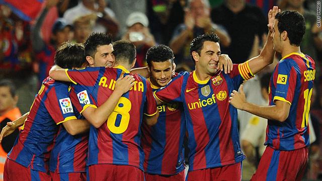 Barcelona's David Villa (L) is mobbed after scoring the winner against Sporting Gijon.