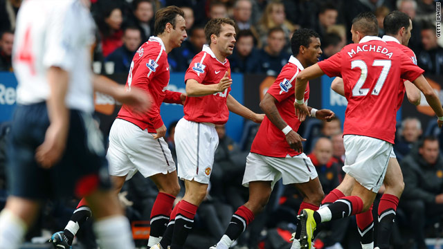 Owen celebrates his equalizing goal with Manchester United teammates at the Reebok.