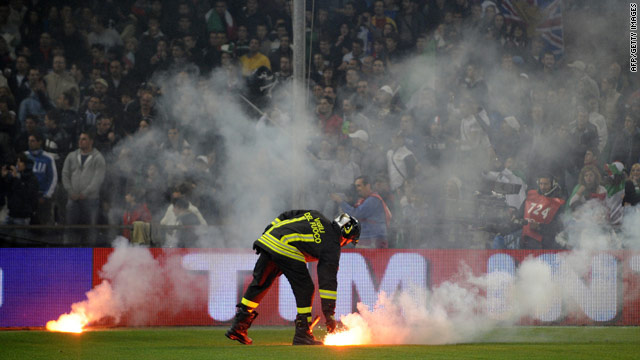 A fireman collects one of the flares thrown onto the pitch that forced the Italy v Serbia match to be abandoned.