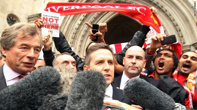 Liverpool Chairman Martin Broughton, left, leaves the High Court Wednesday as fans celebrate.
